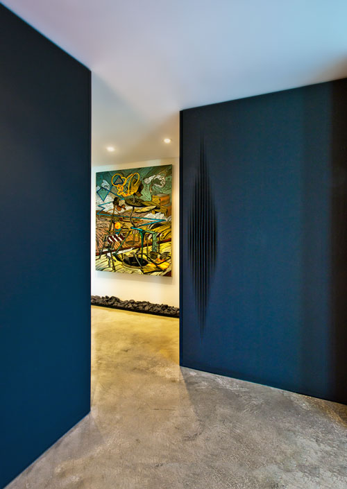 Entry: Clad with Black Metal Doors, Enclosing Mechanical Room, Laundry and Guest Bathroom